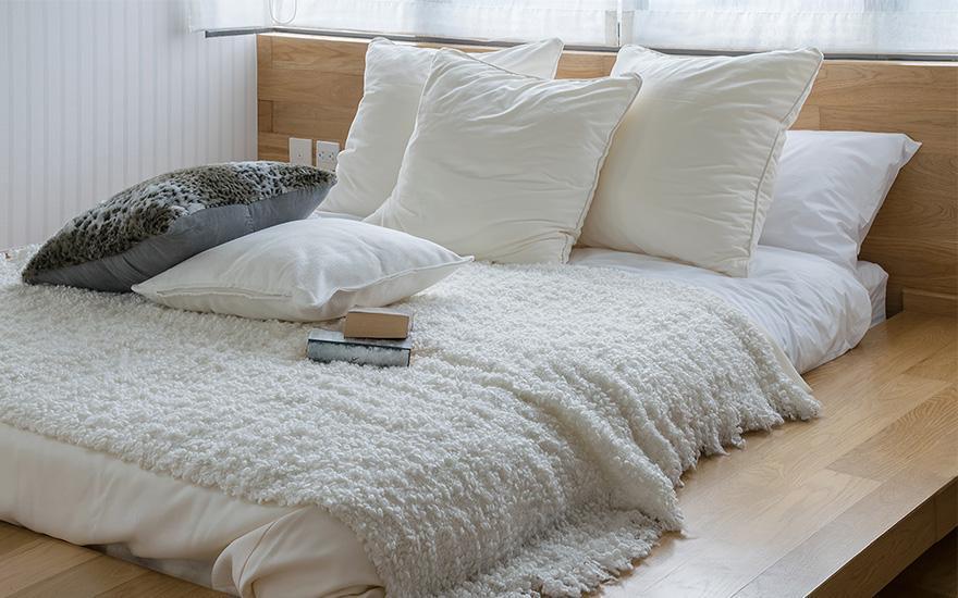 Duże łóżko zbiałym pokryciem
